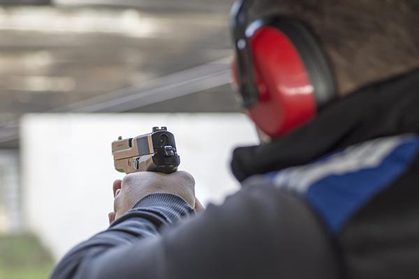Shooting with Gun at Target in Shooting Range. Man Practicing Fire Pistol Shooting.